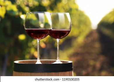 Glasses with red wine on barrel outdoors. Space for text