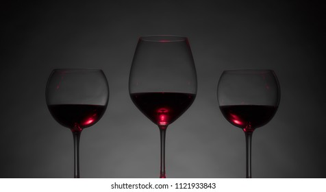 Glasses of red wine on a dark background.
