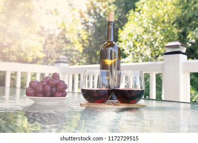 Glasses of red wine on outdoor table during summer
