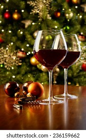 Glasses of red wine on table with Christmas tree in background