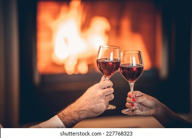 glasses of red wine and romantic fireplace