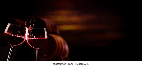 Glasses with red wine toast, in the dark background are wine barrels