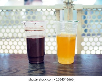 Glasses of refreshing drink; dark cocao and passionfruit tea place of the wooden table with selective focus.