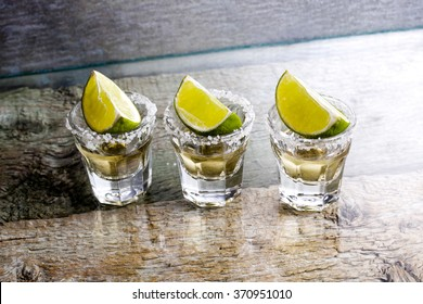 Glasses of silver and gold tequila with lime in a bar
