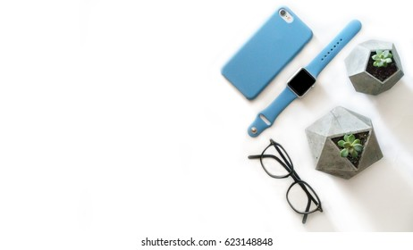 Glasses, smartphone, smart watches, office plant top view  flat lay composition with free copy space on the left side.