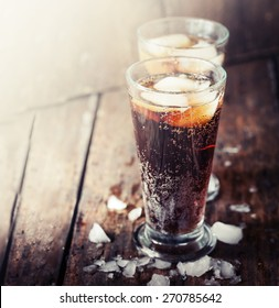 Glasses with soft drink on wooden background