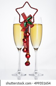 Glasses of sparkling champagne with christmas decoration on white background