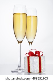 Glasses of sparkling champagne with red gift box on white background