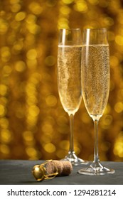 Glasses of sparkling wine on the background of golden bokeh.Celebration theme with champagne still life