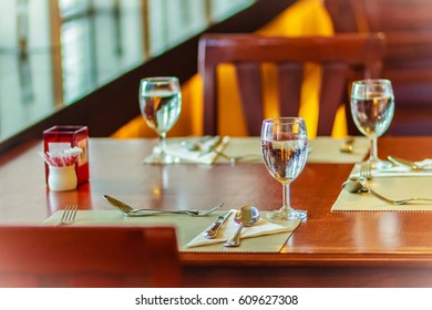 Glasses, spoon, frog, knife, napkin and plates on table setting for meeting and celebrating decoration.