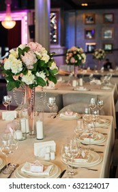 Glasses stand on the square table prepared for wedding dinner