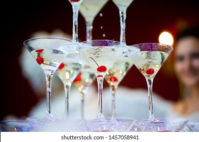 glasses standing in the center of the pyramid with champagne on the background of blurry people