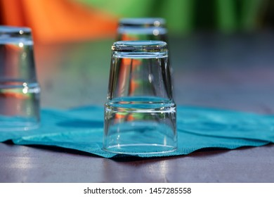 Glasses are standing upside down during golden hour on a turquoise napkin on a table.