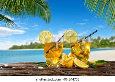 Glasses of summer ice tea drink on beach