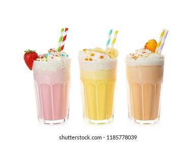 Glasses of tasty milk shakes on white background