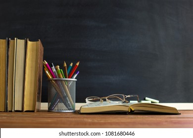Glasses teacher books and a stand with pencils on the table, on the background of a blackboard with chalk. The concept of the teacher's day. Copy space.