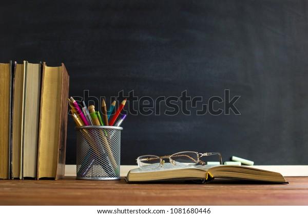 Очки учителя книг и подставка с карандашами на столе, на фоне доски с мелом. Понятие дня учителя. Пространство для копирования.