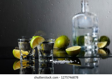 Glasses of tequila with lime and salt on the black reflective background. Alcohol in glasses before wet glass with water drops.