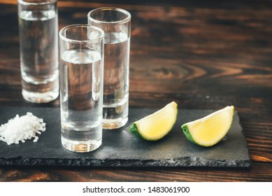 Glasses of tequila with lime wedges on the stone board