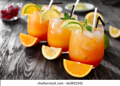 Glasses of Tequila Sunrise cocktail on wooden table
