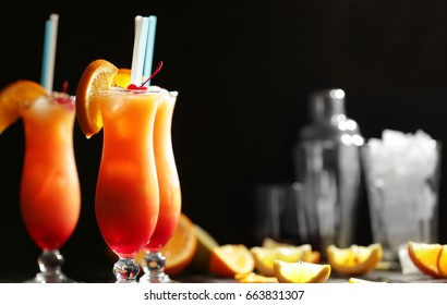 Glasses of Tequila Sunrise cocktail with orange slices on dark background