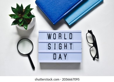 Glasses that correct eyesight, magnifying glass, notepads, green plant and light box with text WOLD SIGHT DAY on a white background. Flat lay. Holiday concept.