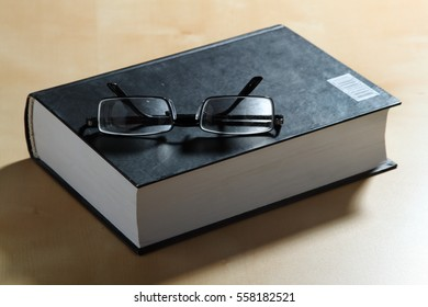 Glasses and a thick book in hardcover.