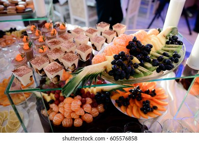 Glasses with tiramisu and dish with fruits stand on glass box