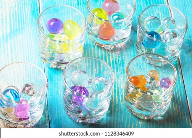 in glasses under alcohol expanded the colored rubber balls, a blue wooden background