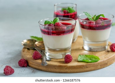 Glasses with vanilla Panna cotta, berry sauce, fresh raspberry and mint on wooden serving board, selective focus.