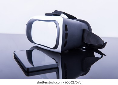 Glasses of virtual reality next to a smartphone on reflective black surface