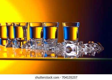 Glasses of vodka with ice on a glass table in bar .