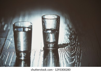glasses of vodka are on the table made of wood