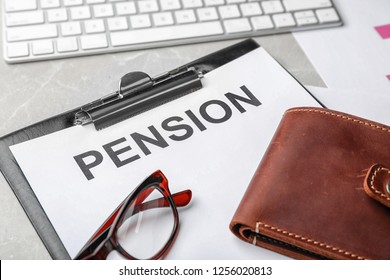 Glasses, wallet and paper with word PENSION on table