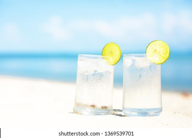 glasses of water with lemon on the beach sand  at hot summer day