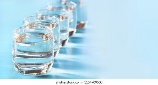 Glasses of water on blue. Close up. Copy space. Water balance for healthy and detox.