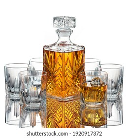 Glasses of  whiskey with a decanter on white background