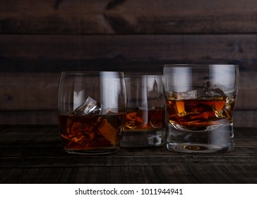 Glasses of whiskey with ice cubes on wooden table background