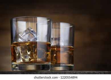 Glasses with whiskey and ice cubes on brown background