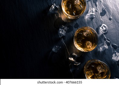 Glasses of whiskey with ice cubes on dark table