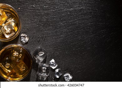 Glasses of whiskey with ice on black stone table. Top view with copy space