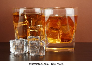 Glasses of whiskey and ice on brown background