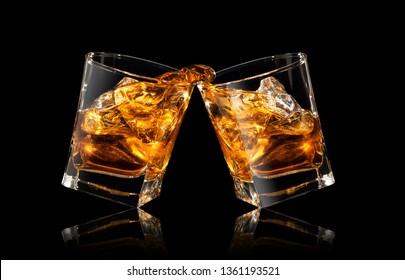 glasses of whiskey making toast with splashes on black background