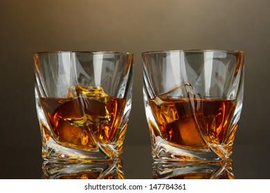 Glasses of whiskey, on dark background