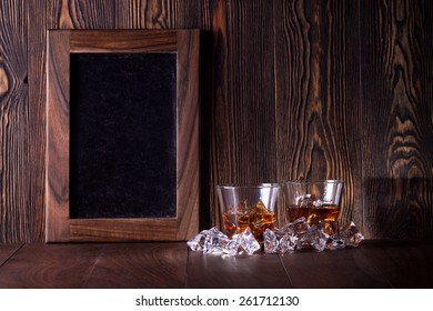 Glasses of whiskey on wood background