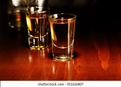 glasses of whiskey shots on wooden surface