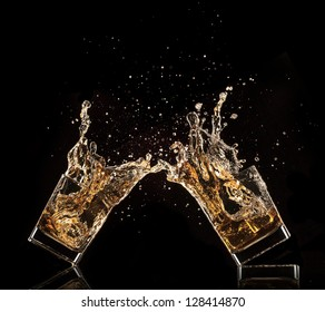 Glasses of whiskey with splash, isolated on black background