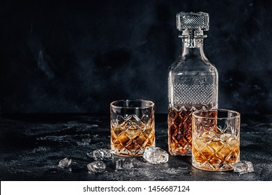 Glasses of the whiskey with a square decanter on a black stone background.