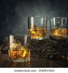 glasses of whisky with ice on a wooden table