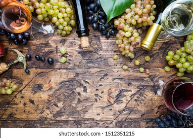 Glasses with white, red and pink wine and ripe grapes on wooden background, top view